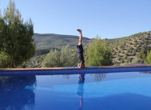 Doing a headstand by the swimming pool